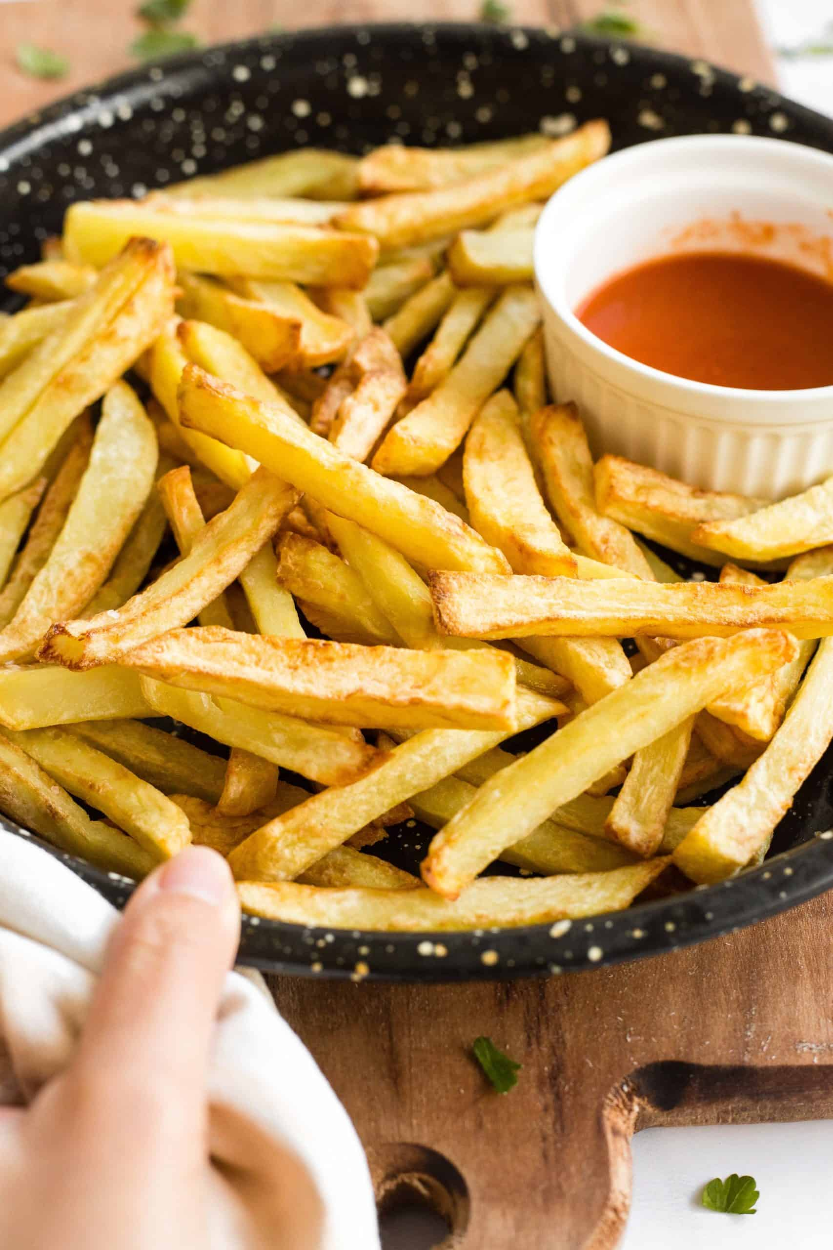 Hand holding a plate of crispy air fryer fries.