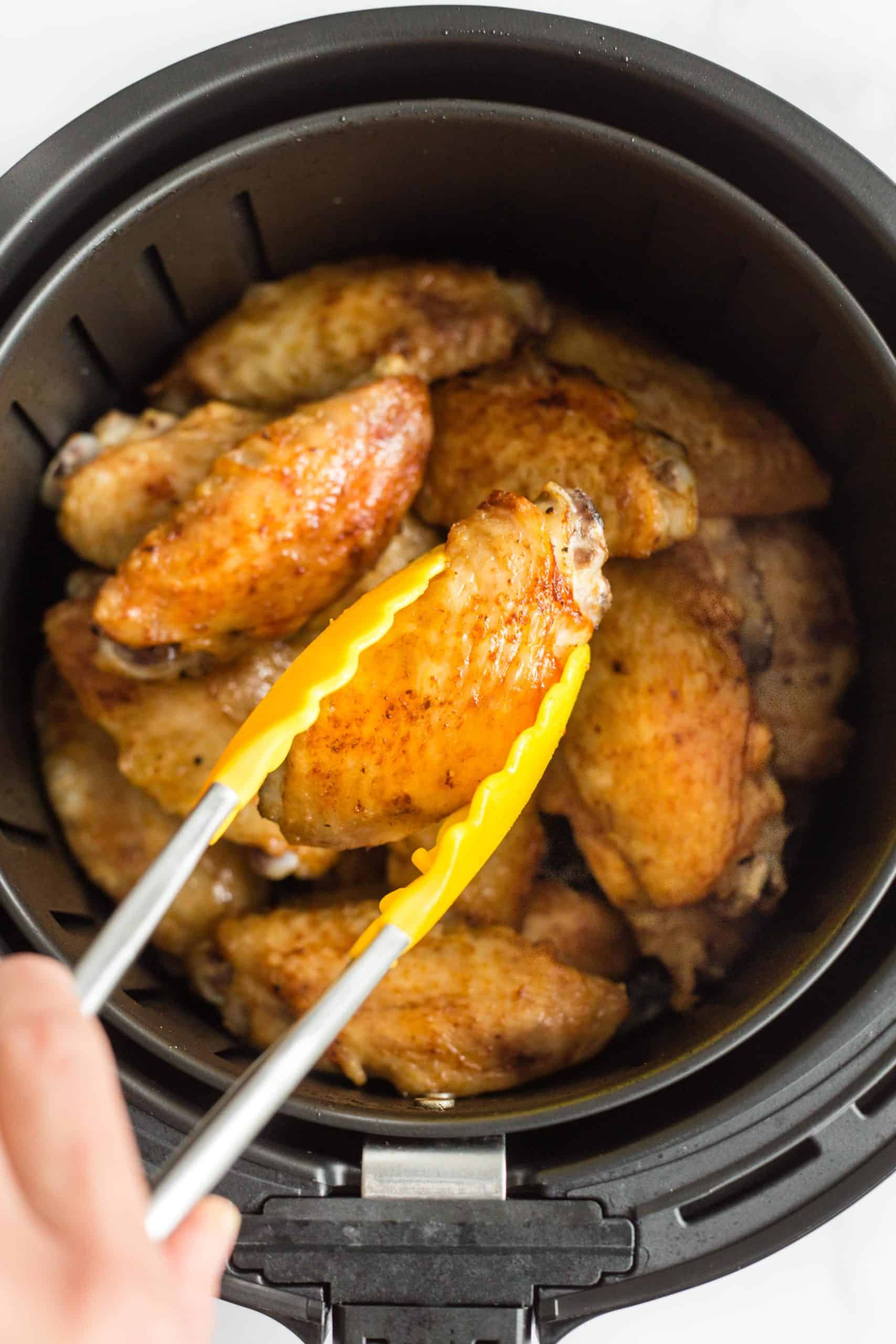 Picking up a crispy chicken wing from the air fryer basket.