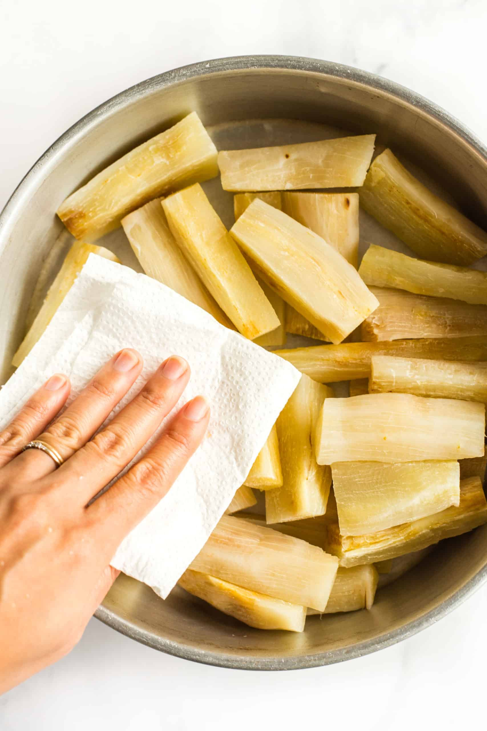 Patting the yuca wedges dry after boiling them in water.