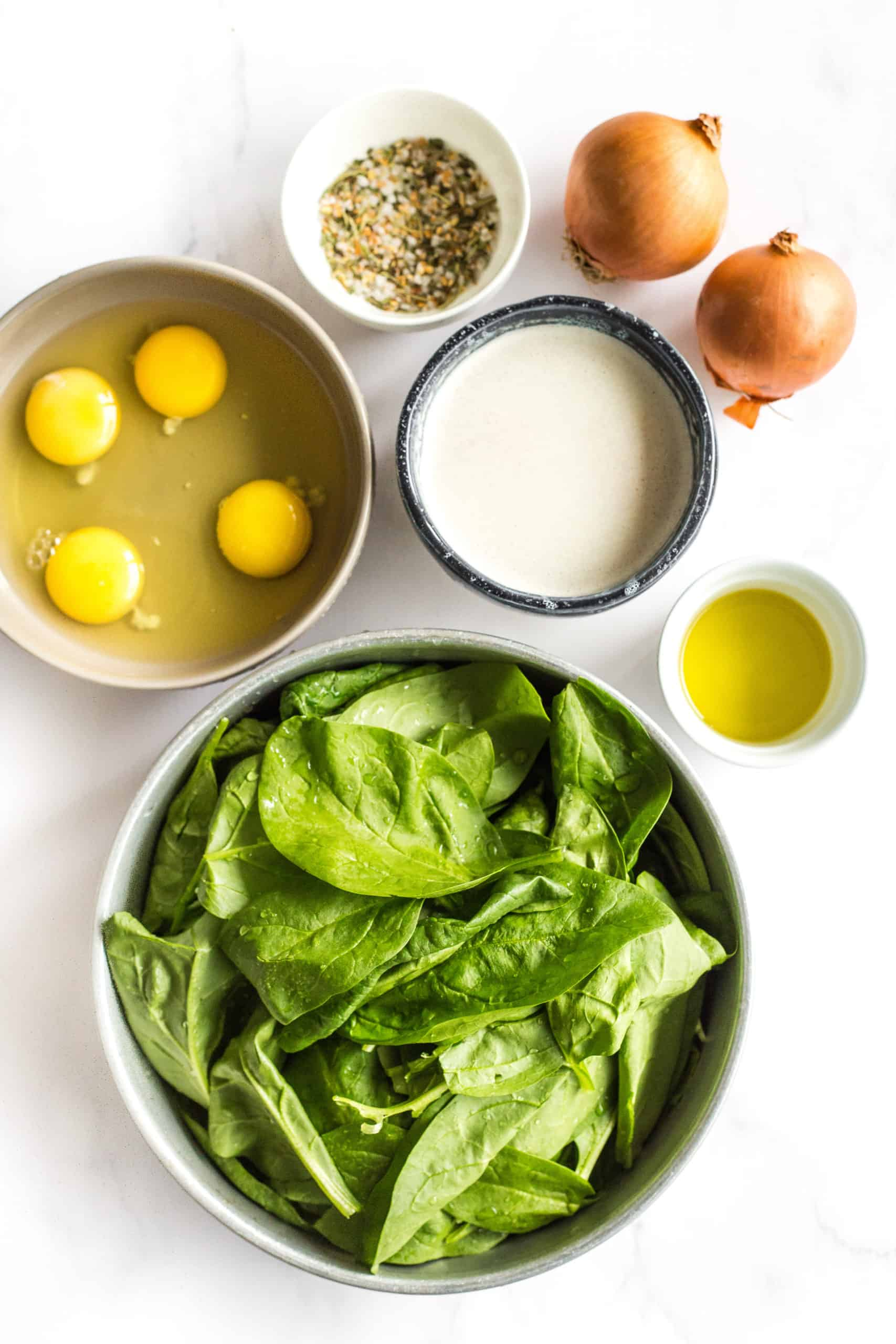 Ingredients for crustless spinach quiche on a marble board