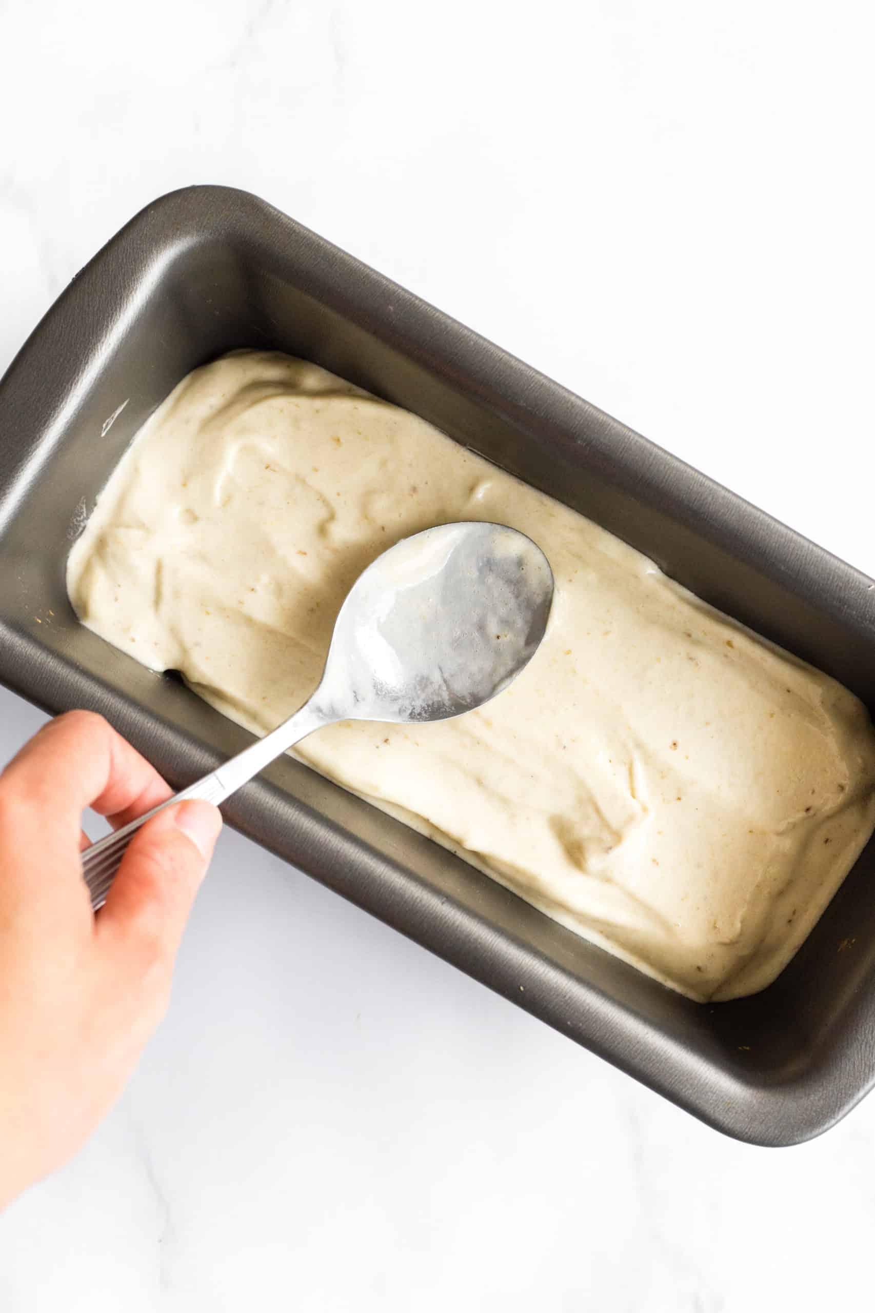 Using a spoon to spread out banana ice cream in a loaf pan to be frozen