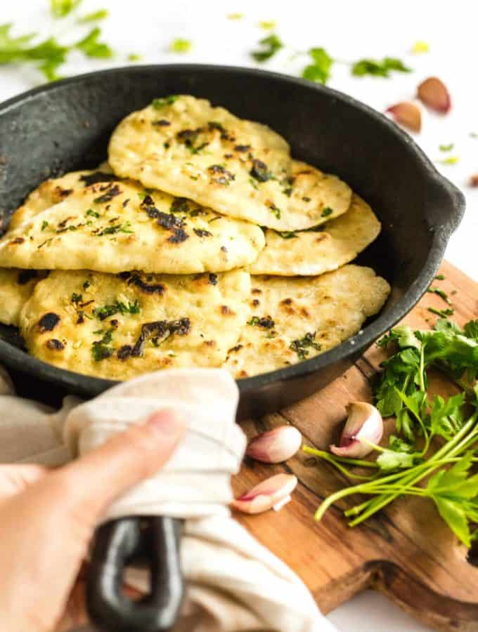 Gluten-free naan in a cast iron skillet on a wooden board