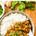 Slow cooker lentil curry in a bowl on a wooden board