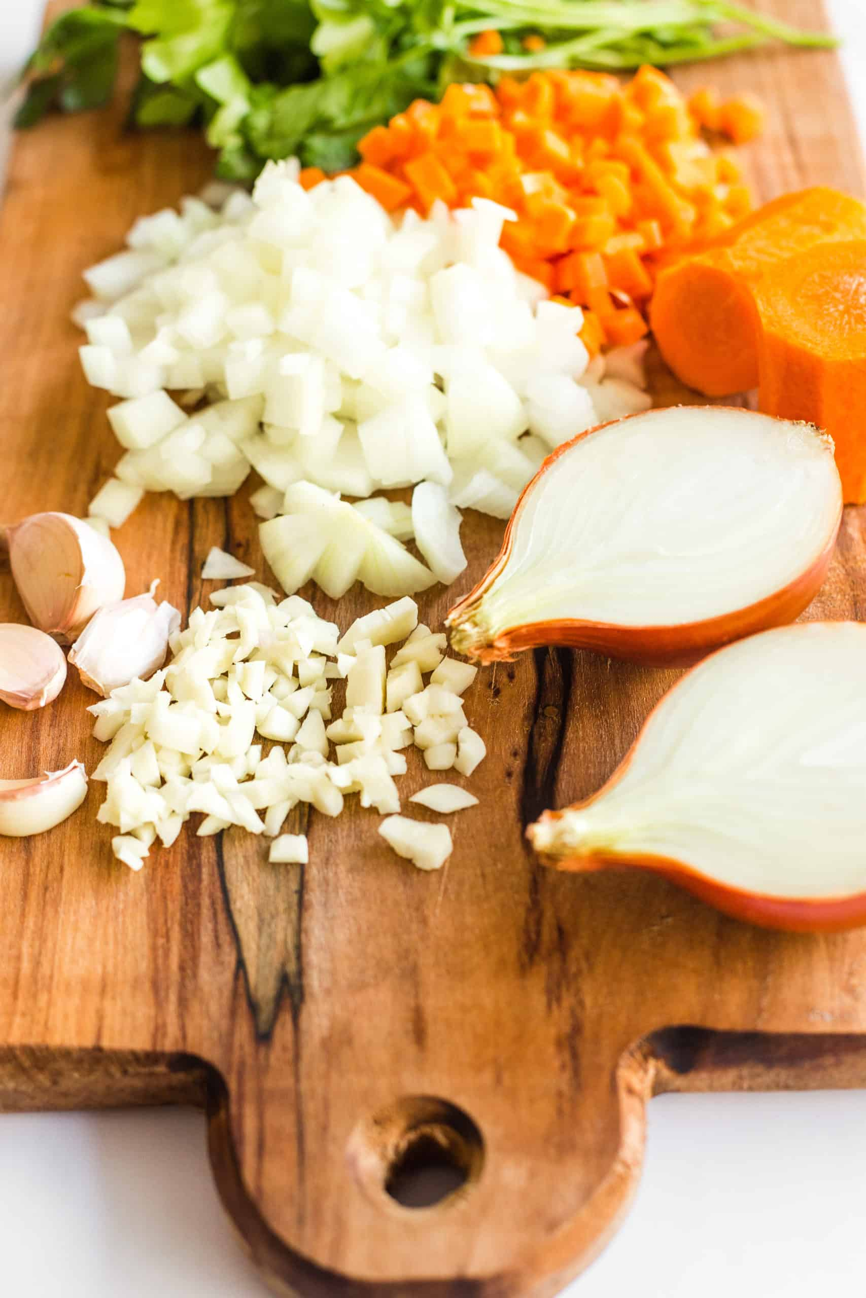 Ingredients for slow cooker lentil curry on a wooden chopping board