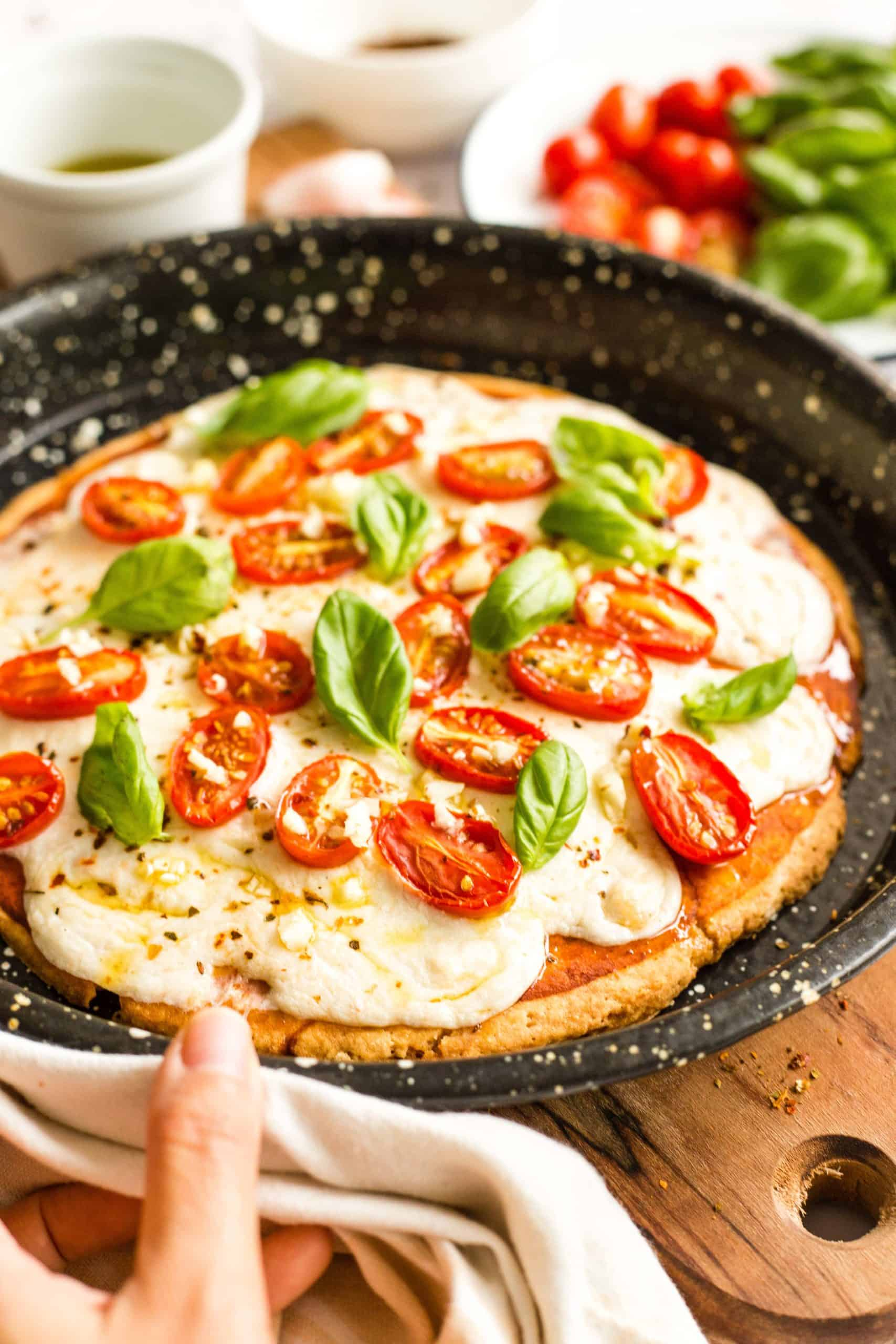 Hand holding a pizza pan with a freshly baked gluten-free caprese pizza.