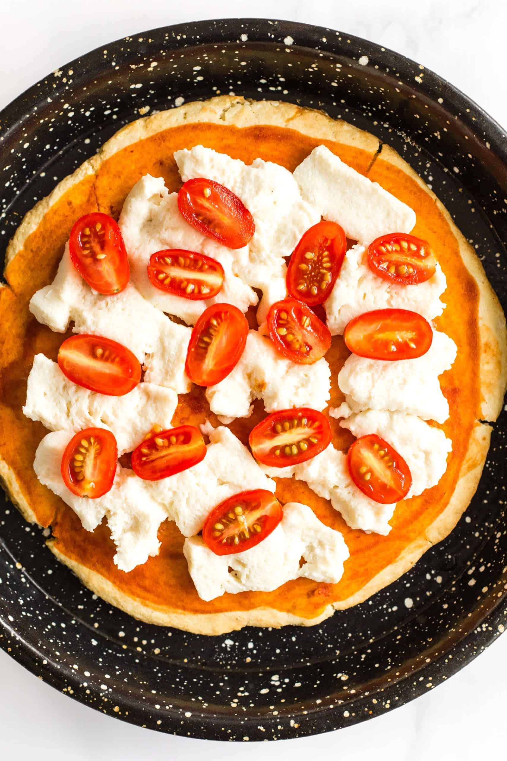 Gluten-free pizza crust with mozzarella cheese and cherry tomato halves.