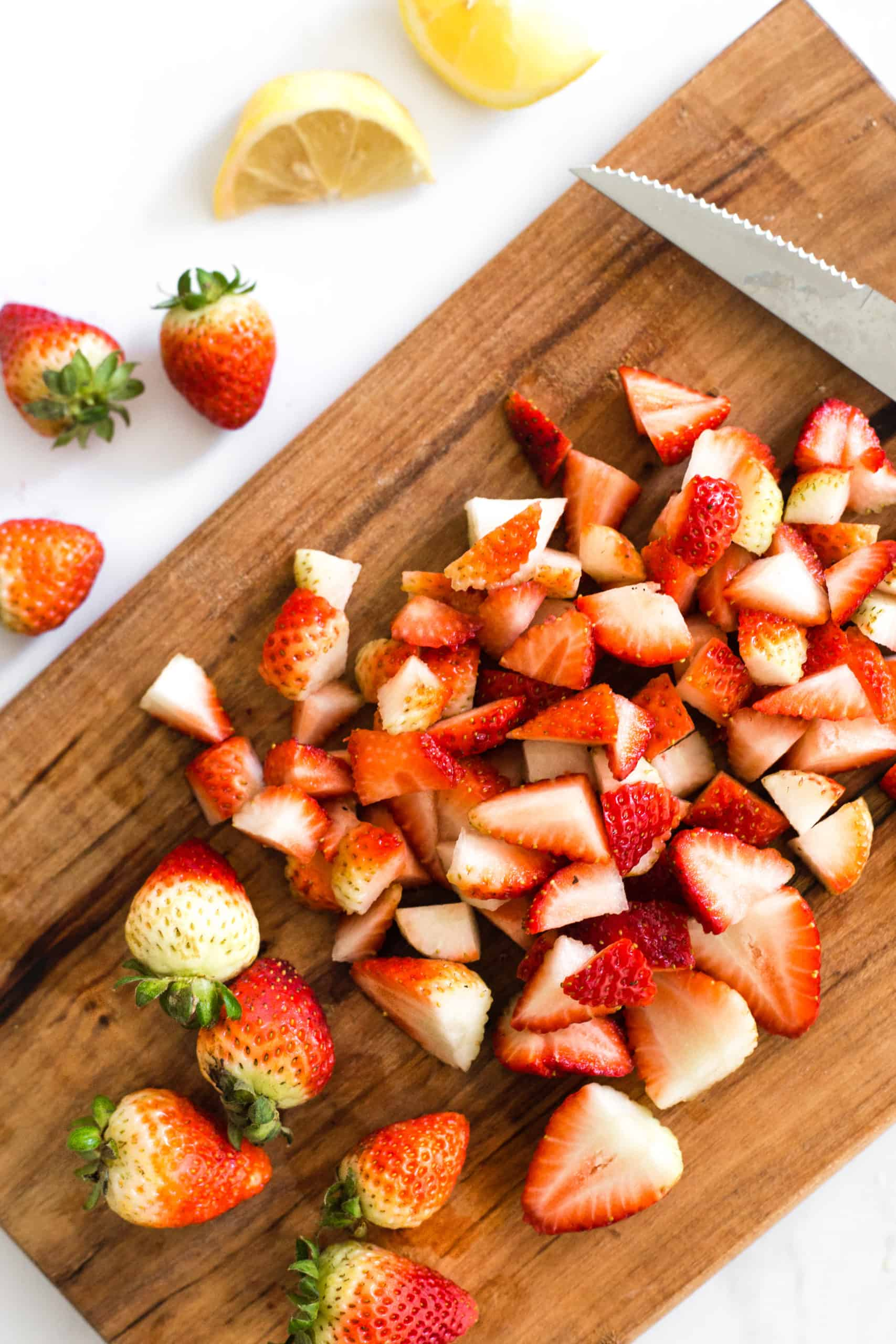 Cut strawberries on a wooden chopping board