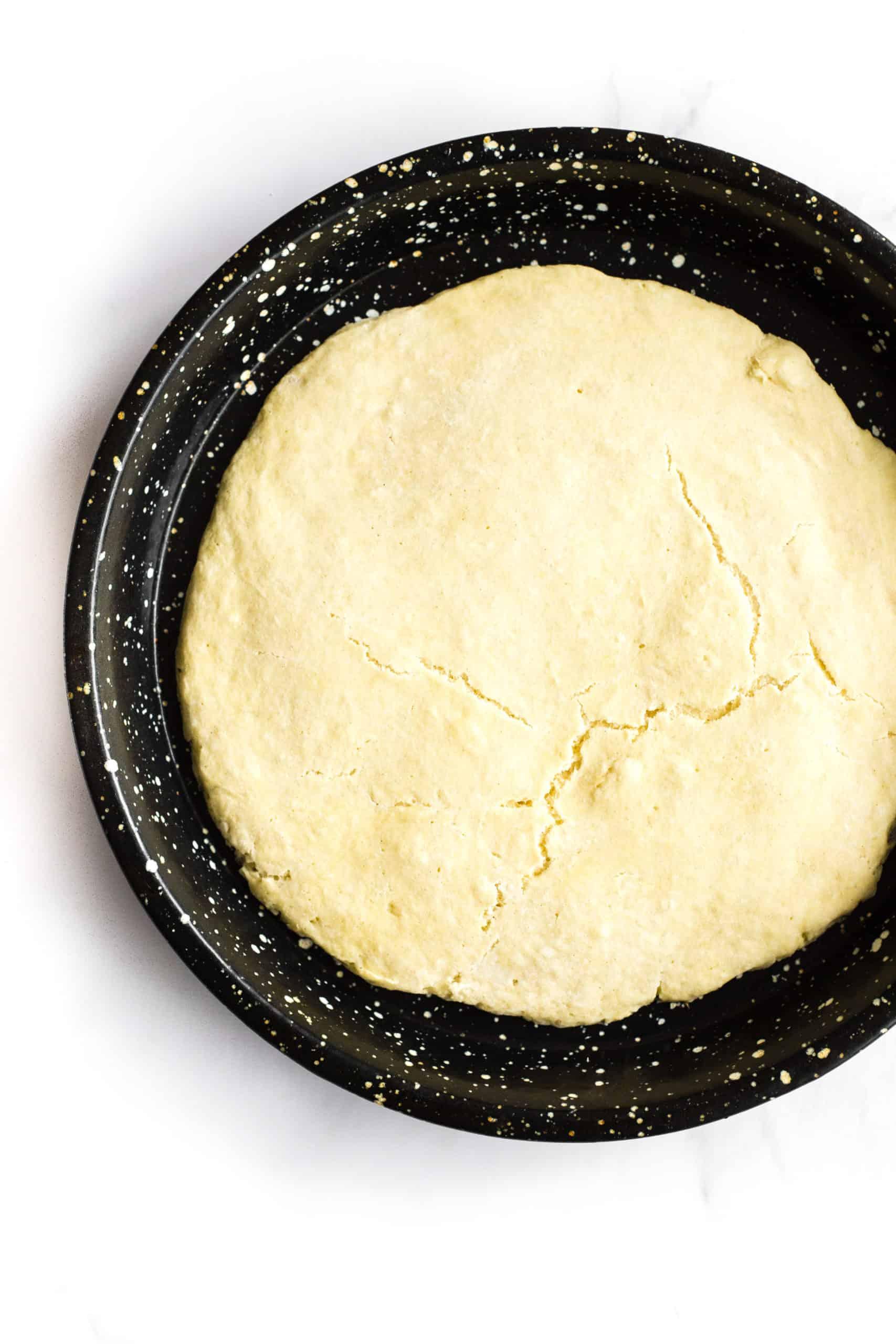 Gluten-free pizza crust in a pizza pan.